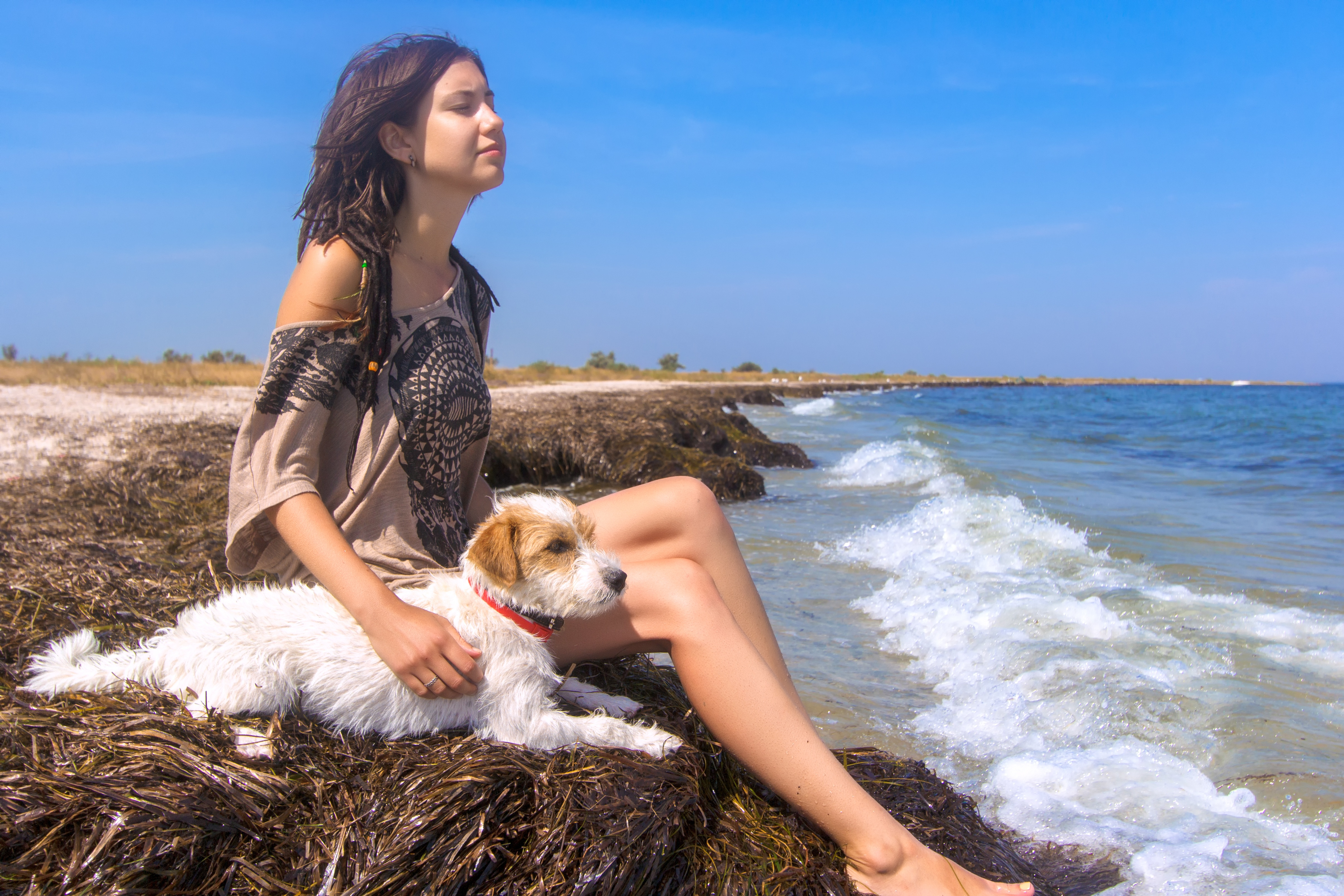 Young gal with her dog by the beach.